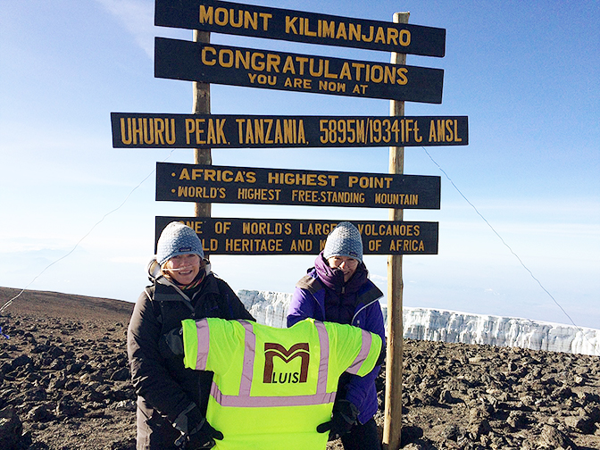 Two women at the summit of Mt. Kilimanjaro, Africa, standing in front of the sign at the peak.